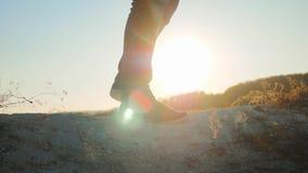 Chaussures de marche d'espadrilles de jambes de pieds de touristes d'homme augmentant le coucher du soleil de grimpeurs d'aventur banque de vidéos