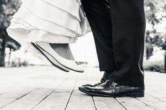 Chaussures de mariage en se tenant et en volant des couples Images stock
