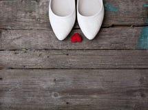 Chaussures de mariage et coeur rouge sur le fond en bois Photos libres de droits