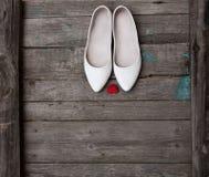 Chaussures de mariage et coeur rouge sur le fond en bois Photographie stock
