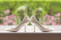 Chaussures de mariage par une fenêtre Photographie stock