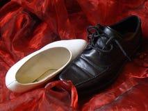Chaussures de mariage se blottissant sur la soie rouge Photos stock