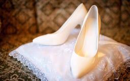 Chaussures de mariage se tenant sur un oreiller blanc Photo stock