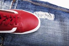 Chaussures de mode avec des chaussures Espadrilles et dentelles rouges avec des jeans sur un fond blanc Photographie stock