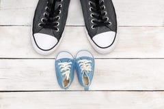 Chaussures de père et de fils sur le fond en bois blanc, jour de father's Photos libres de droits