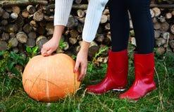 Chaussures de pluie de potiron d'automne et en bois rouges avec le fond de leavs Photos stock