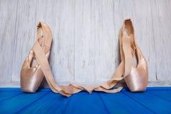Chaussures de pointe de ballet sur le fond en bois de couleur lumineuse avec le noeud photographie stock libre de droits