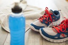 Chaussures de sport avec la boisson et la serviette d'énergie Photographie stock
