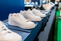 Chaussures de sport blanches sur les boîtes bleues à vendre Photographie stock libre de droits