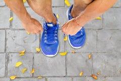 Chaussures de sport de laçage d'homme sur le plancher en parc avec les feuilles sèches photos stock