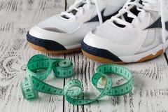 Chaussures de sport et bande de mesure sur le fond blanc Chaussures de sport et Photo libre de droits