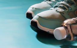 Chaussures de sport et bouteille bleues de l'eau sur le fond bleu avec la cannette de fil Photographie stock libre de droits