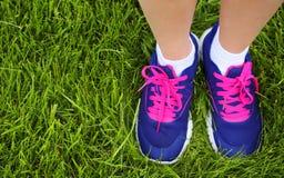 Chaussures de sport sur les pieds femelles sur l'herbe verte closeup Photographie stock