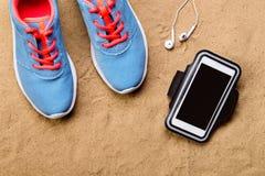 Chaussures de sports, écouteurs, smartphone contre le sable, tir de studio Photos libres de droits