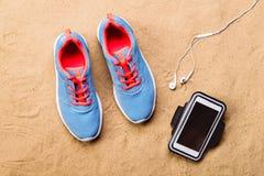 Chaussures de sports, écouteurs, smartphone contre le sable, tir de studio Photo stock