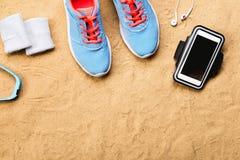 Chaussures de sports, écouteurs, smartphone contre le sable, tir de studio Images stock