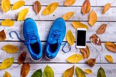 Chaussures de sports Smartphone, écouteurs, feuilles d'automne En bois blanc Photo stock
