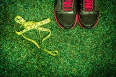 chaussures de sports sur le fond de l'herbe verte Photographie stock libre de droits