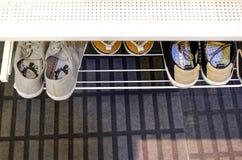Chaussures de sports sur un support dans le couloir photo stock