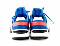 Chaussures de tennis bleues sur le backgound blanc Photo libre de droits