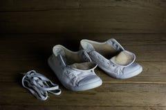 Chaussures de toile blanches sur le fond en bois, toujours la vie Image stock