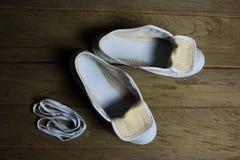 Chaussures de toile blanches sur le fond en bois, toujours la vie Photographie stock