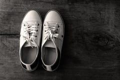 Chaussures de toile blanches sur le ton noir et blanc de vieux plancher en bois Image libre de droits