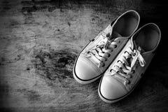 Chaussures de toile blanches sur le vieux plancher en bois Image libre de droits