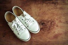 Chaussures de toile blanches sur le vieux plancher en bois Images stock