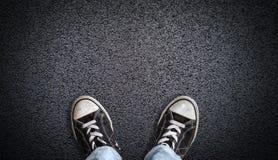 Chaussures de toile de port d'ado sur le fond d'asphalte avec l'espace de copie Images stock