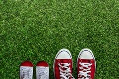 Chaussures du père et du fils étendus sur l'herbe verte en parc Photo stock