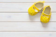 Chaussures du ` s d'enfants pour une fille nouveau-née jaune Wh léger de fond Photos stock
