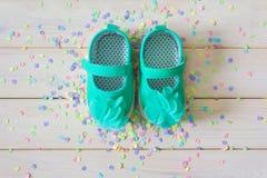 Chaussures du ` s d'enfants pour une fille nouveau-née turquoise Lumière de fond Photographie stock