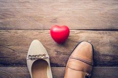Chaussures du ` s de chaussures et d'hommes du ` s de femmes avec des coeurs placés sur un flo en bois Photographie stock libre de droits
