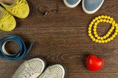 Chaussures du ` s de femmes, perles jaunes, ceinture bleue et écouteurs noirs plats Photographie stock libre de droits