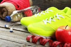 Chaussures, eau, ruban métrique et écouteurs Image stock