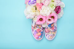 Chaussures en caoutchouc avec des fleurs à l'intérieur sur le fond lumineux Photographie stock