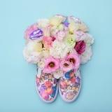 Chaussures en caoutchouc avec des fleurs à l'intérieur sur le fond lumineux Photographie stock libre de droits