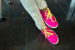 Chaussures en caoutchouc avec les dentelles jaunes sur les jambes femelles Image stock