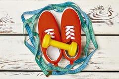 Chaussures en caoutchouc, haltère et bande de mesure Image stock