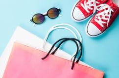 Chaussures en caoutchouc rouges avec des sacs et des lunettes de soleil d'expédition Photos stock