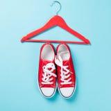 Chaussures en caoutchouc rouges avec les dentelles et le cintre blancs Photos libres de droits