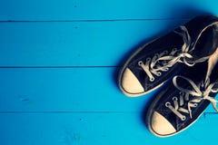 Chaussures en caoutchouc sales sur le fond en bois bleu Image libre de droits