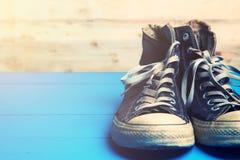 Chaussures en caoutchouc sales sur le fond en bois bleu Photo stock