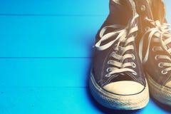 Chaussures en caoutchouc sales sur le fond en bois bleu Images libres de droits