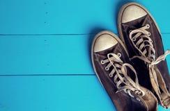 Chaussures en caoutchouc sales sur le fond en bois de coeur Photos libres de droits