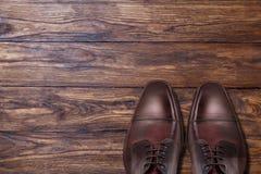 Chaussures en cuir brunes masculines classiques sur le bois Photographie stock libre de droits