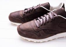 Chaussures en cuir de Brown avec des dentelles sur le fond en bois Image libre de droits