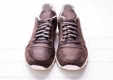Chaussures en cuir de Brown avec des dentelles sur le fond en bois Images libres de droits