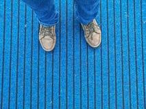 Chaussures en cuir de Brown avec des jeans se tenant sur le tapis bleu Photo stock